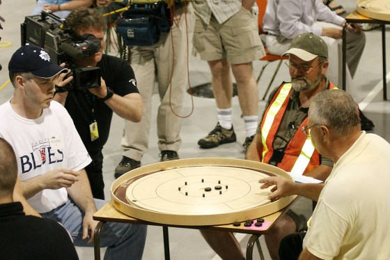 Cameraman films the 2004 World Crokinole Championship between Brian Cook and Joe Fulop as neon-vest wearing referee watches