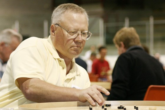 Grey-haired and with glasses Joe Fulop concentrates over a crokinole board at the 2004 World Crokinole Championship