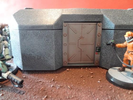 Rust wash is visible on steel bunker door as well as paint splash below control panel