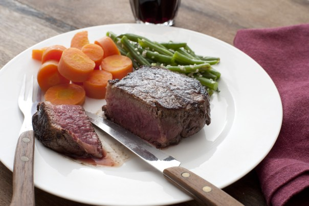 Delicious medallion of thick juicy fillet steak sliced through and served with carrots and green runner beans on a white plate