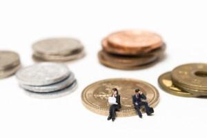 お金の硬貨の上に座って仕事に悩む人間
