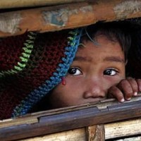 A Bhutanese refugee looks from a bamboo hut in the Ti Mai camp, Nepal. Photograph: Desmond Boylan/Reuters
