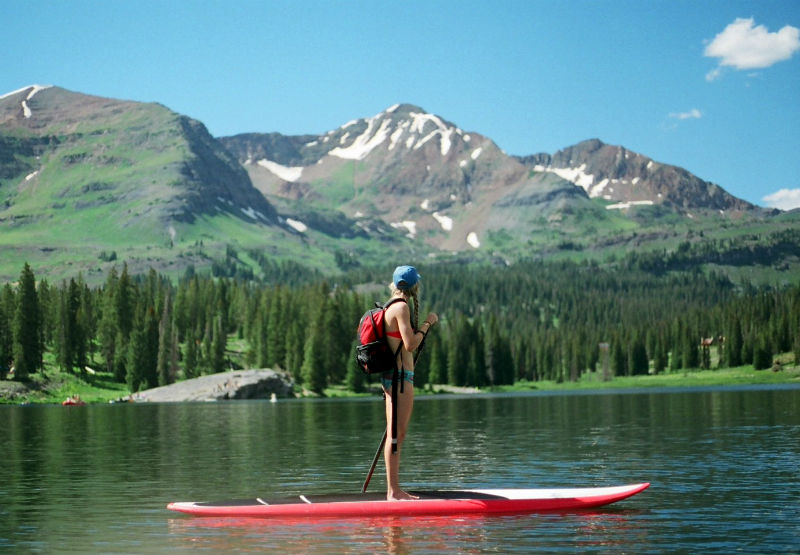 girl on paddleboard with mountains and trees