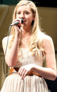 """Arielle Tiensvold,  senior of Rushville, solos during the song """"Avenue C"""" in Memorial Hall. — Photo by Ashley Swanson"""