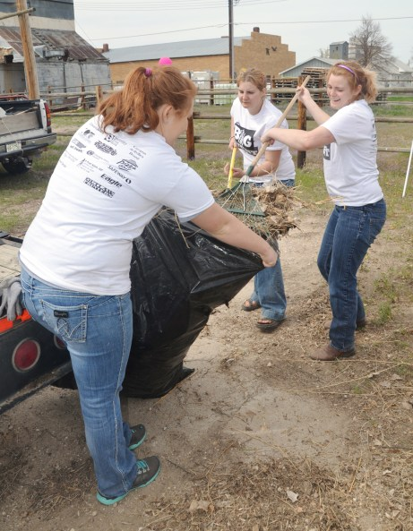 Meg Peterson, left, 19, freshman of Haigler; Sara Rollenhagen 19, sophomore of Wallace; and Kayla Bunch, 21, senior of Rapid City, South Dakota, work together to collect raked leaves into a trash bag in Crawford. —Photo by Janelle Kesterson