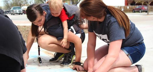 From left, Nikki Schmidt, 23, graduate student of Merino, Colorado; her son Rowan; and Stephanie Wilson, 21, junior of Albuquerque, New Mexico, use sidewalk chalk to raise awareness about trash that gets washed down the city drains during Saturday's The Big Event in Chadron. —Photo by Janelle Kesterson