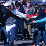 CSC students and faculty, and Job Corps students slap hands with Chadron elementary students Monday as they join the Martin Luther King Jr. Day March down Shelton St.—Photo by Melanie Nelson