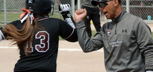 Kayla Michel (13), sophomore of Brighton, Colorado, fist bumps Head Softball Coach Robert Stack after hitting a home run Sunday during a game against Adams State University, Alamosa, Colorado, at the CSC Softball Field. — Photo by Jordyn Hulinsky