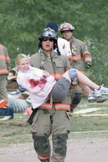 "Fort Carson Firefighter Matthew Sebesta carries injured ""victim"" Chelsea Keene to safety."