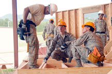 A civil engineering mentor works with two cadets during construction of a Navajo home. Photo by Bill Evans