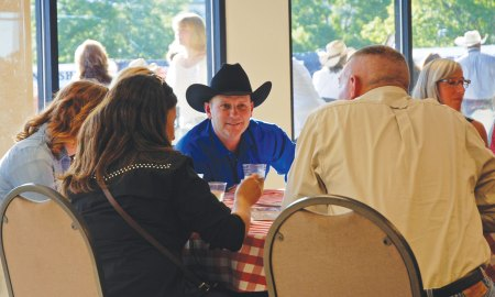 (U.S. Air Force photo by Dave Smith) COLORADO SPRINGS, Colo. – Col. Douglas Schiess, 21st Space Wing commander, talks with tablemates at the 75th Annual Pikes Peak or Bust Rodeo July 10 during Air Force Space Command night. Fifty recipients were selected by local Air Force base commanding officers for their outstanding service to receive a Salute Our Troops challenge coin and recognition during the night's rodeo opening events.