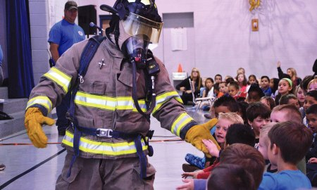 U.S. Air Force photo/Brian Hagberg Firefighter Justin Greco, Ellicott Fire Department, greets children during an assembly at Ellicott Elementary School in Ellicott, Colorado, Monday, Oct. 10, 2016. Greco arrived in street clothes and donned his firefighter gear in front of the children to show them how quickly firefighters gear up and to make them more comfortable seeing a firefighter in full protective equipment.