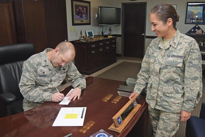 (U.S. Air Force photo by Staff Sgt. Tiffany Lundberg) PETERSON AIR FORCE BASE, Colo. — Col. Doug Schiess, 21st Space Wing commander, signs the Air Force Assistance Fund forms contributing funds for Airmen in need of emergency assistance, April 18, 2017, at Peterson Air Force Base, Colo. The AFAF's campaign goal is to raise $69,350 from Team Pete to provide financial emergency assistance to retired Airmen, surviving spouses and Airmen.