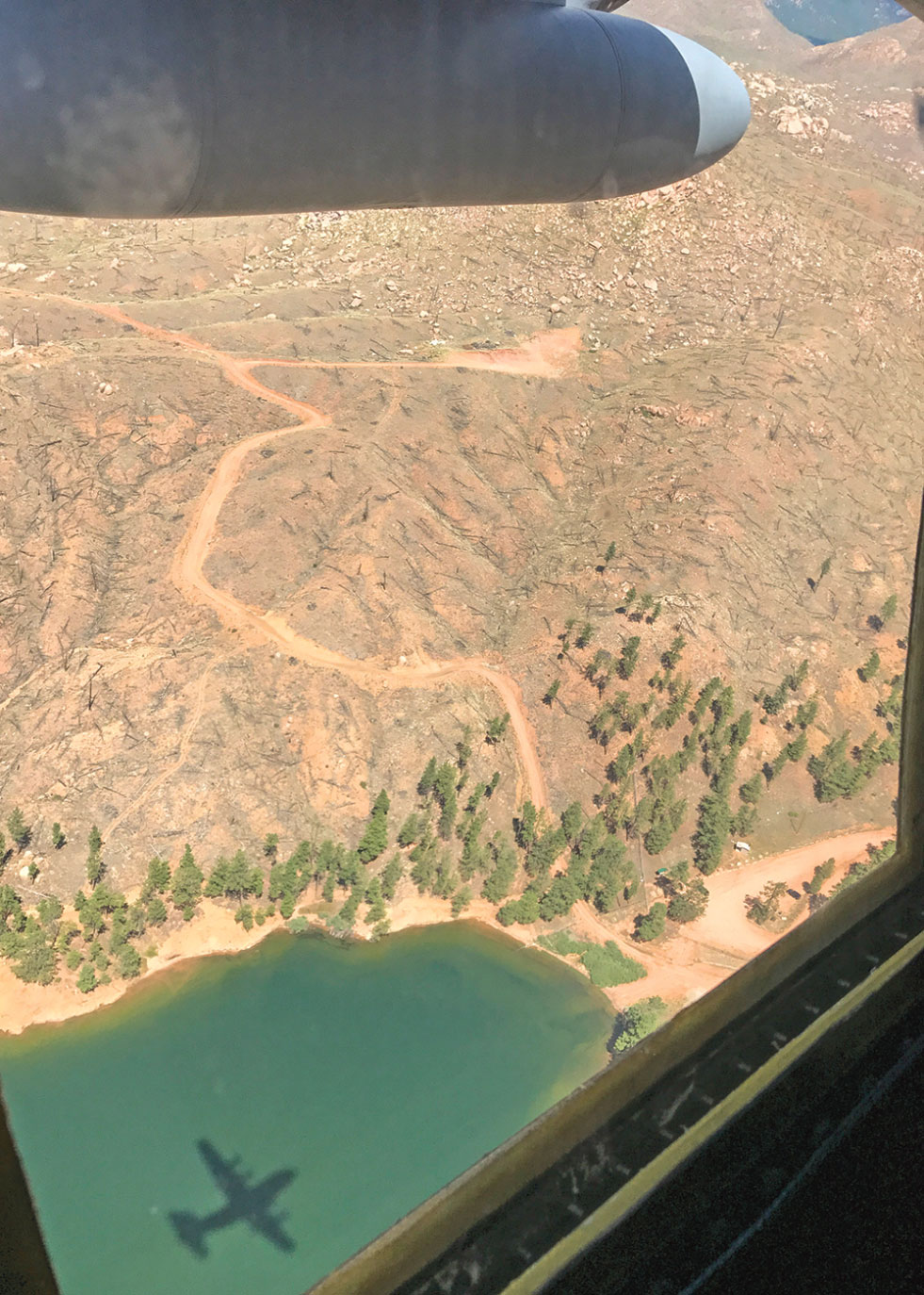 (Courtesy photo by 1st Lt. Will Jones) Colorado Rockies, Colo. — The shadow of a C-130H Hercules is seen over a lake in the Colorado Rockies July 28, 2017. Two Hercules from the 94th Airlift Wing, Dobbins Air Reserve Base, Ga. participated in high-altitude airdrops alongside other Air Force Reserve C-130 wings as part of a training exercise.