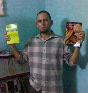El pastor Mario presentando dos libros que ha donado a la biblioteca