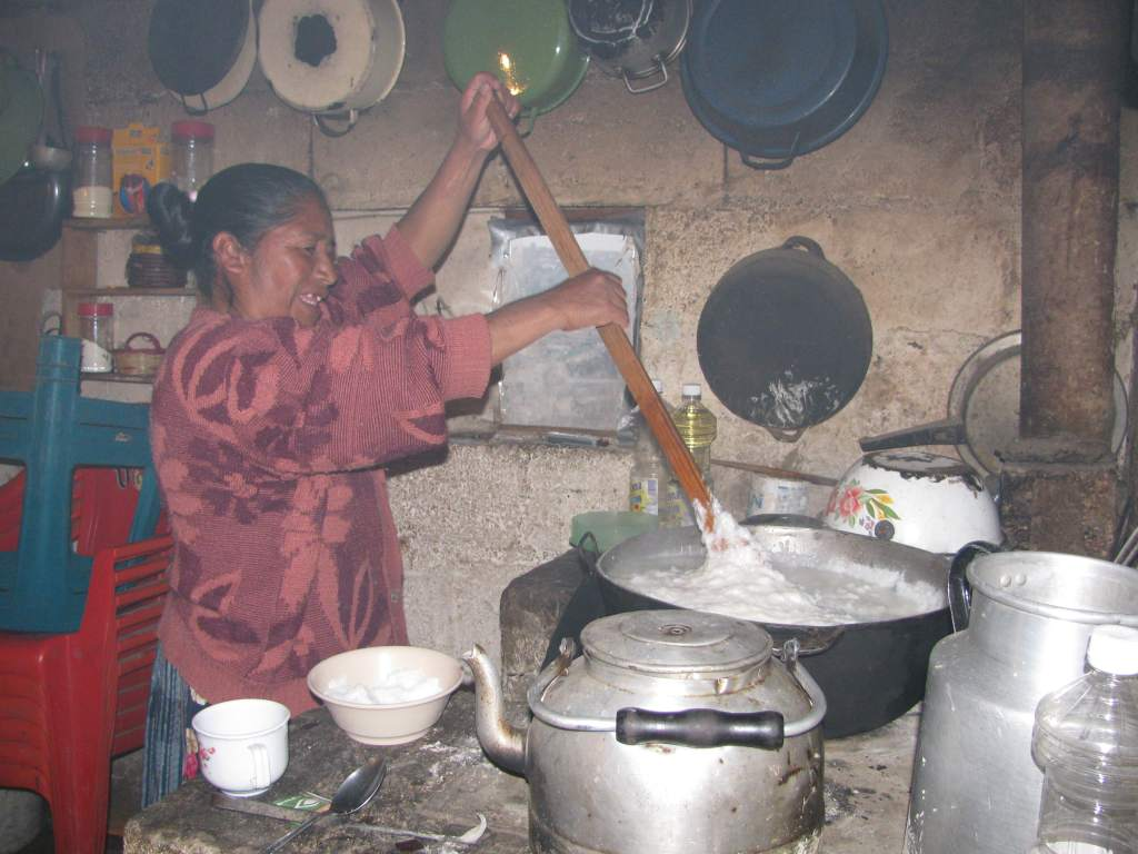 Grandma stirring the pots in a humble Xela home, Guatemala