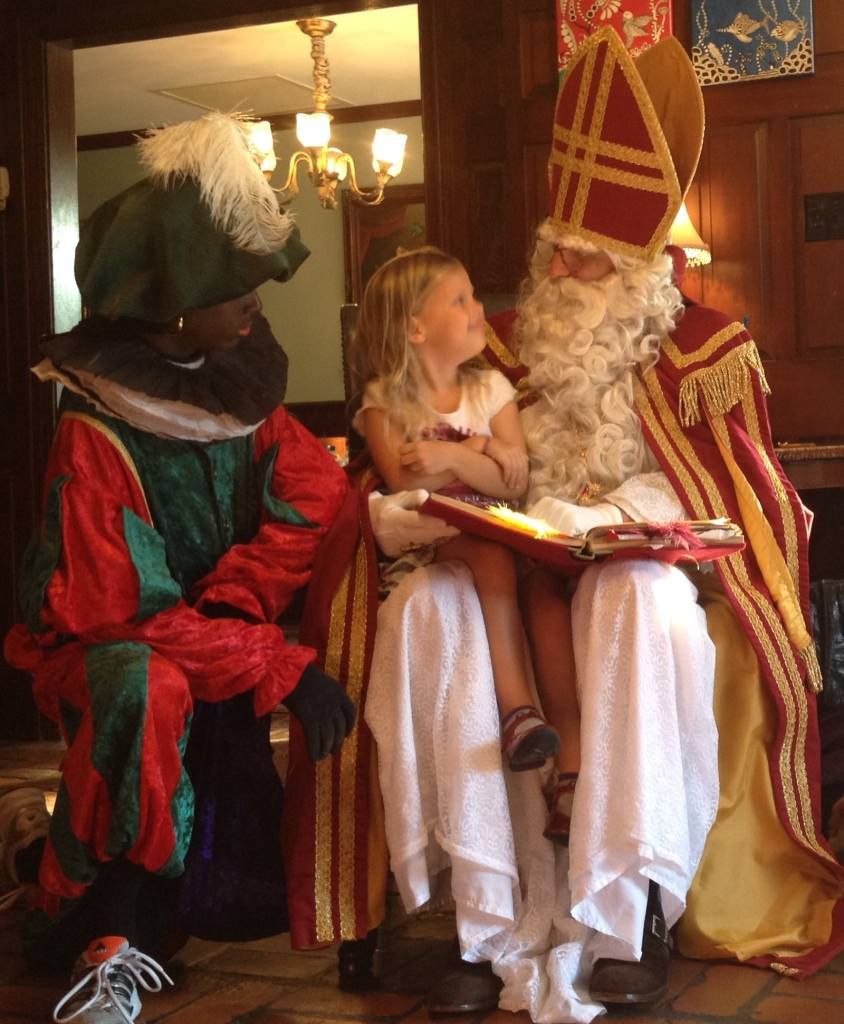 Little girl sitting on Sinterklaas' lap