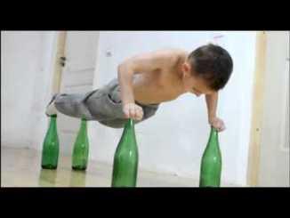 Niño haciendo flexiones sobre botellas