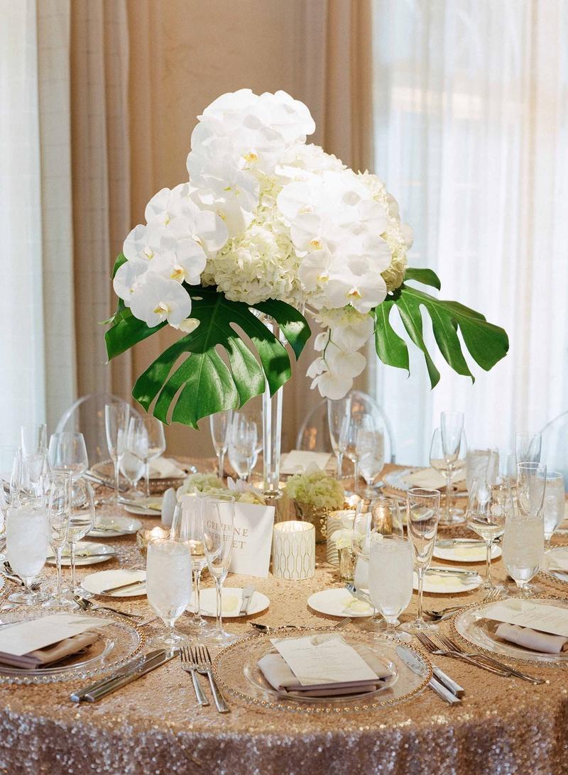 gold sequin linen with tropical centerpiece wedding linens Destination wedding modern beach glam reception with sequin linen orchid hydrangea philodendron