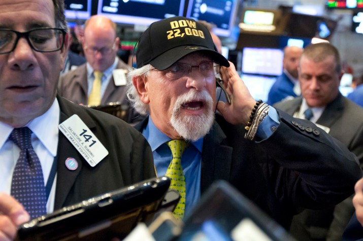 "Trader Peter Tuchman, center, wears a ""Dow 22,000"" hat as he works on the floor of the New York Stock Exchange, Wednesday, Aug. 2, 2017. (Richard Drew/AP)"
