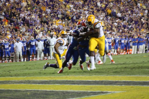 LSU rb Fournette takes two Gators into the endzone.