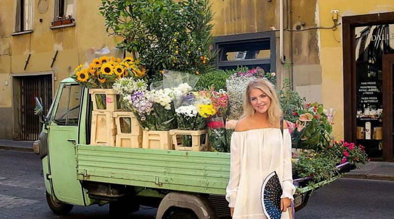 Paige Neubauer stands by a flower cart in Spain. 2016. (Lynn Neubauer).