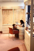 Optician fitting child with glasses at Jules Stein Eye Center