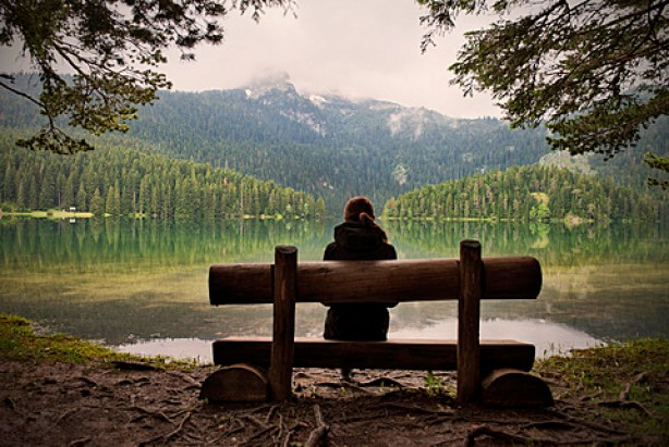 Young woman sitting on a bench looking across the Black Lake Crno jezero in Durmitor National Park, Zabljak, Montenegro, Western Balkan, Europe