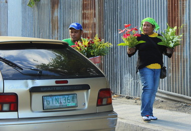 FLOWER VENDORS.  Flower vendors, who get up as early as three in the morning to prepare for the day, show their arrangements to a potential customer.  All Soul's Day is the other time aside from Valentine's Day that sales of flowers peak.  (davaotoday.com photo by Medel V. Hernani)