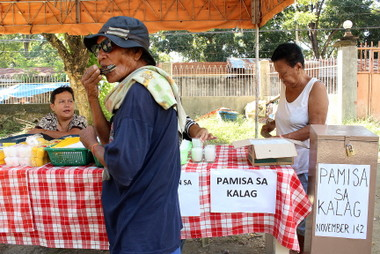 MASS FOR THE SOULS.  A booth is installed outside the Tibungco Public Cemetery to facilitate those who want to offer mass for their dead.  Meanwhile, an old man plays harmonica to earn money.  (davaotoday.com photo by Medel V. Hernani)