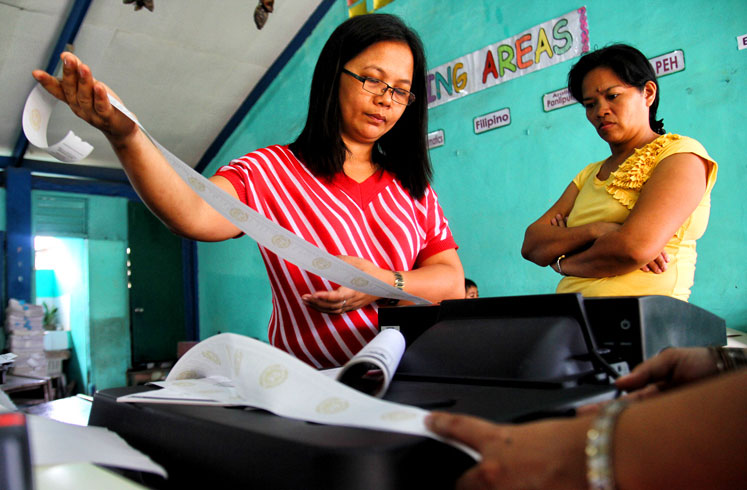 A Board of Election Inspector in one of the clustered precincts in Davao City's Cesario Villa Abrille Elementary School tests the PCOS machine during the Final Testing and Sealing Monday.  (davaotoday.com photo by Ace R. Morandante)