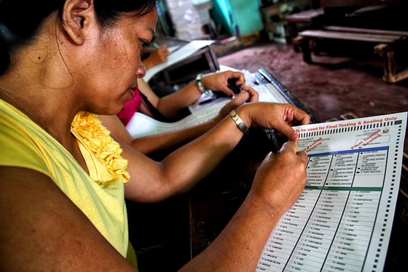 TEST.  A poll watcher casts her vote during the final testing and sealing of PCOS (precinct count optical scanner) machines Monday in Davao City's Cesario Villa Abrille Elementary School (formerly Bucana Elementary School).  (davaotoday.com photo by Ace R. Morandante)