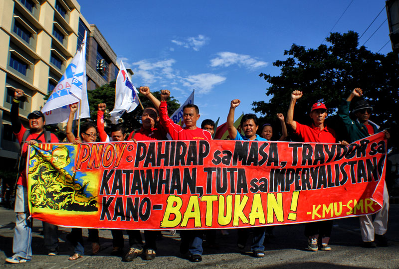 WITH CLENCHED FISTS. Leaders of progressive organizations in Davao City lead the march of more than a thousand participants for the International Labor Day celebration Wednesday. Labor center Kilusang Mayo Uno said if the Aquino government continues to ignore the demands of the working class and the people, currents of resistance are inevitable. (davaotoday.com photo by Ace R. Morandante)