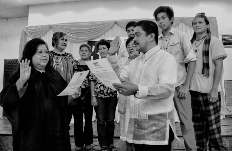 OATH-TAKING.  Bayan Muna Party's Representative-elect Carlos Isagani Zarate takes oath before Judge Virginia Europa Friday in Garden Oases, Davao City.  Behind him are his family and representatives from the groups of lawyers and Lumads in Mindanao.  Zarate said he will continue to fight for the people's welfare and interests, this time in the halls of Congress.  (davaotoday.com photo by Medel V. Hernani)