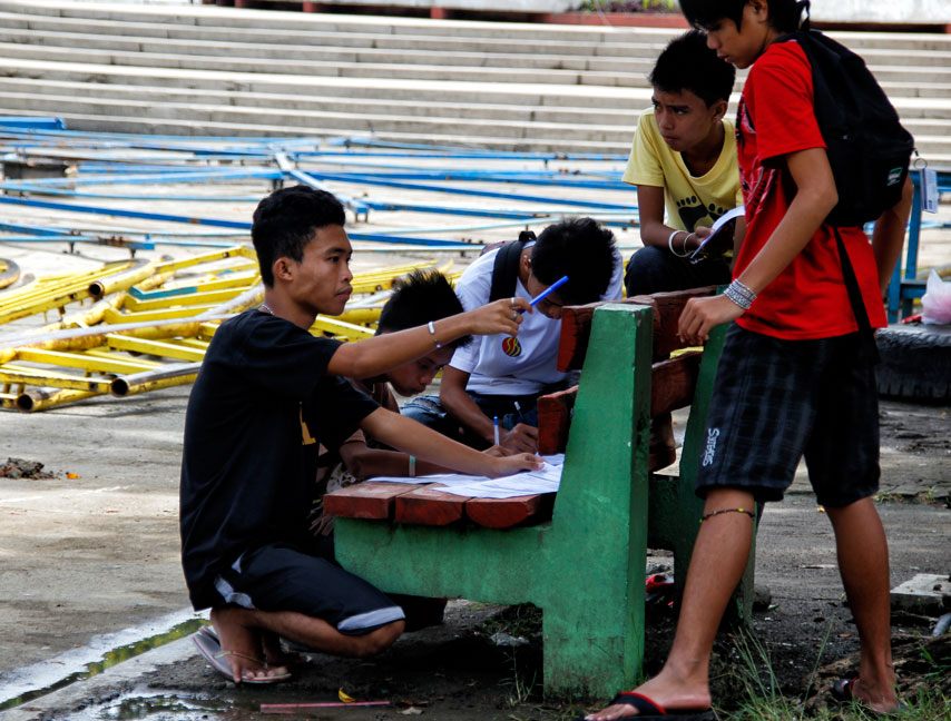 FIRST TIME Youths gathered in a bench to fill up their voter registration forms at Davao's Comelec office in Magsaysay Park as registration deadline draws near on July 31. Barangay and SK (Youth Federation) elections are set this October. (davaotoday.com photo by MEDEL V. HERNANI)