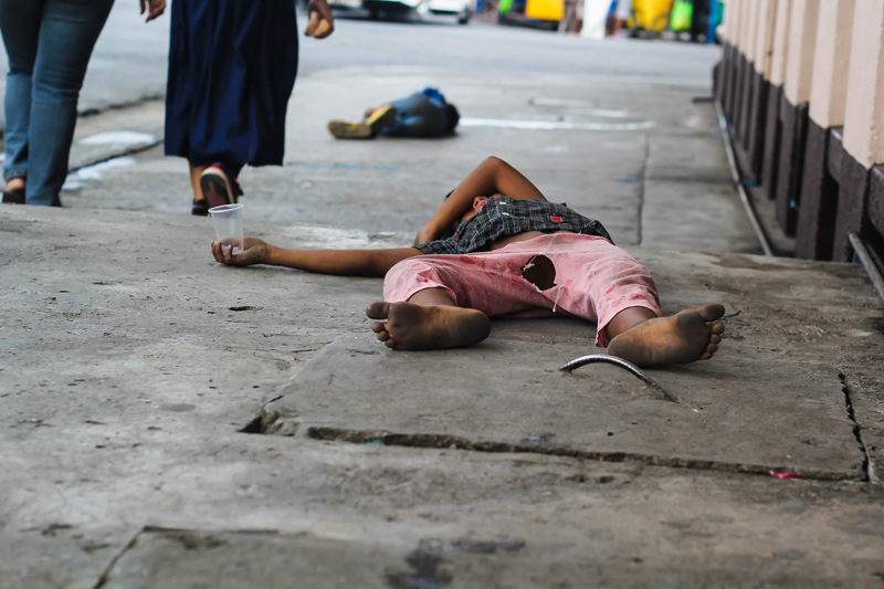 As the public rages over misuse of people's taxes, a beggar in torn pants sleeps off his hunger in a sidewalk along Bonifacio Street. (davaotoday.com photo by Ace R. Morandante)