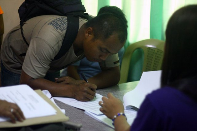 Sonny Cortes, stepfather of slain Roque Antivo, signs his affidavit before the Provincial Prosecution Office in Nabunturan, Compostela Valley. (davaotoday.com photo by John Rizle L. Saligumba)