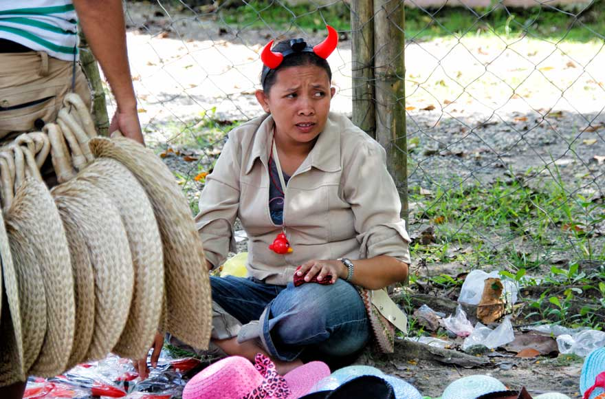 """HORNS OF ATTRACTION A vendor of fans and hats attracts customers for her with her """"devil"""" headband along Tibungco Cemetery during Saturday's observance of All Souls Day. (davaotoday.com photo by Medel V. Hernani)"""