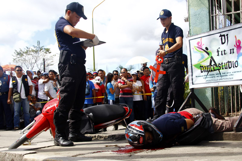RADIOMAN SHOT Police probe the crime scene where radio commentator Rogelio 'Tata' Butalid was shot outside of Radyo Natin Tagum in Sobrecary Street last Wednesday past 9am. (davaotoday.com photo by Earl O. Condeza)