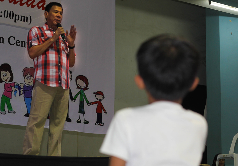 ALL EYES ON MAYOR A boy listens to Mayor Rodrigo Duterte as he gives his message during the city's Christmas treat to poor children last Monday at Almendras Gym. (davaotoday.com photo by Ace R. Morandante)