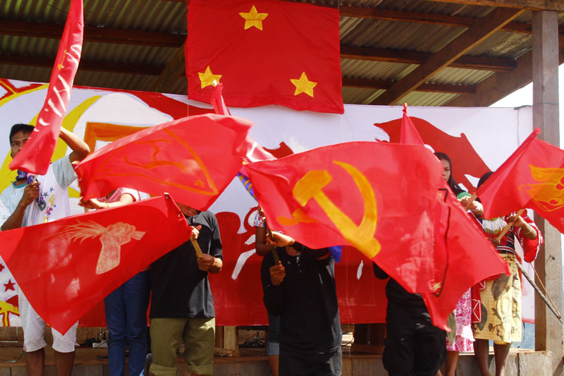 "RED BASE. Representatives of ""revoluationary"" organizations comprising a communist ""revolutionary municipality"" somewhere in Compostela Valley wave flags to signal the opening ceremony of their assembly. (davaotoday.com)"