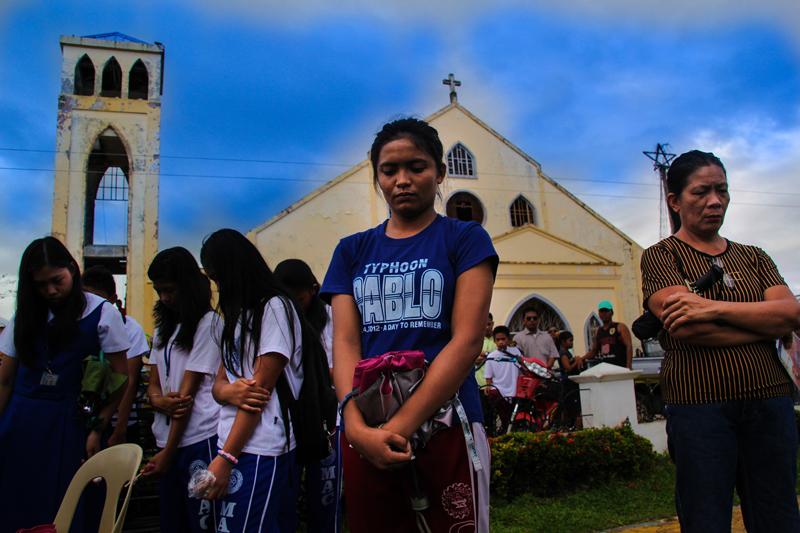 PRAYER  Students and other residents of Cateel, Davao Oriental prayed for the memory of victims of Typhoon Pablo during the first year commemoration of the storm that left around 1,000 dead or missing. (davaotoday.com photo by Ace R. Morandante)