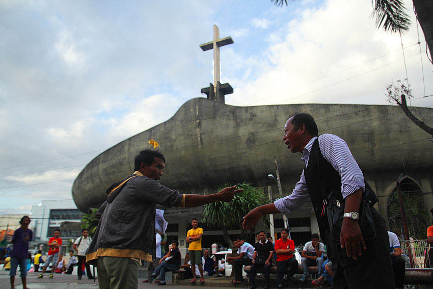 So-called faith defenders from the Jehovah's Witness and Roman Catholic argue in front of San Pedro Cathedral on which one is the real religion. (Ace R. Morandante/davaotoday.com)
