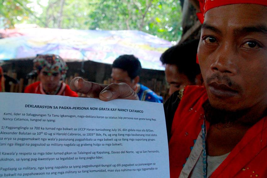 A member of the tribal group Salugpungan Ta Tanu Igkanugon shows their statement calling North Cotabato 2nd District Representative Nancy Catamco as persona non grata. (Ace R. Morandante/davaotoday.com)