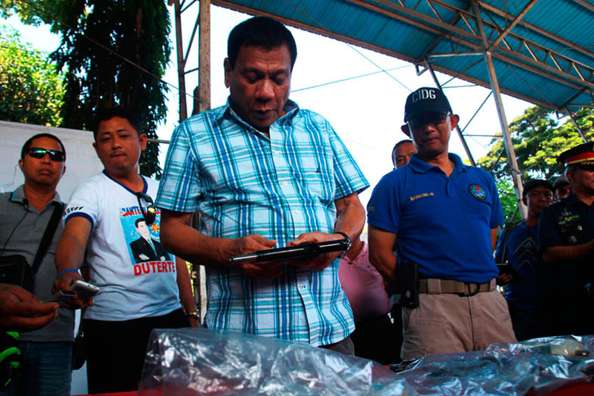 Mayor Rodrigo Duterte checks the confiscated guns owned by the alleged drug pushers rounded-up in a simultaneous raid in Davao City on Wednesday morning. The authorities have confiscated a total of 13 firearms and 10 assorted ammunition. (Ace R. Morandante/davaotoday.com)