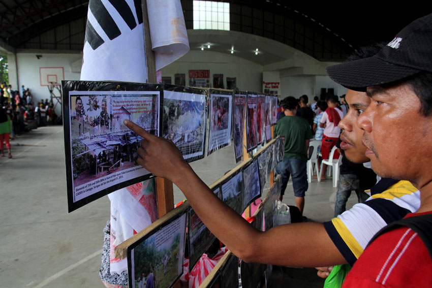 "People who visited the wake of Alcadev director Emerito Samarca look at the photos of the ""Lianga Massacre"" displayed in the Capitol Gym in Butuan City."