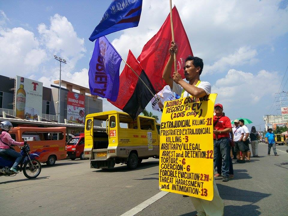 RECORD. A protester holds a placard of the record of human rights violations in Eastern Visayas this year during a protest action held in Tacloban City on Thursday. (Earl O. Condeza/davaotoday.com)