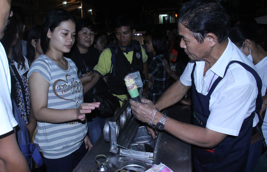 Ice-cream vendor Dionilo dela Torre, 60, is flocked by hundreds of customers along Roxas Avenue who lined up for about 3-5 hours just to buy his ice cream. Customers start to line up as early as 4:00 pm, while Dela Torre arrives at 9:00 pm. (Ace R. Morandante/davaotoday.com)