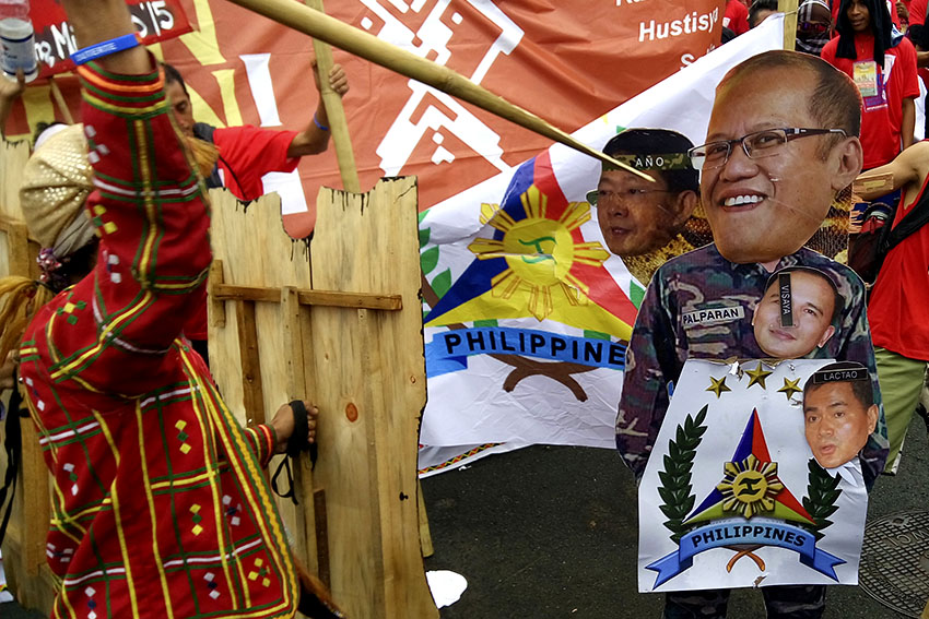 ON POINT. In a cultural act, tribal leaders from Manilakbayan protesters, spread photos of military generals and that of President Aquino in front of Camp Aguinaldo, Monday morning. (Earl O. Condeza/davaotoday.com)