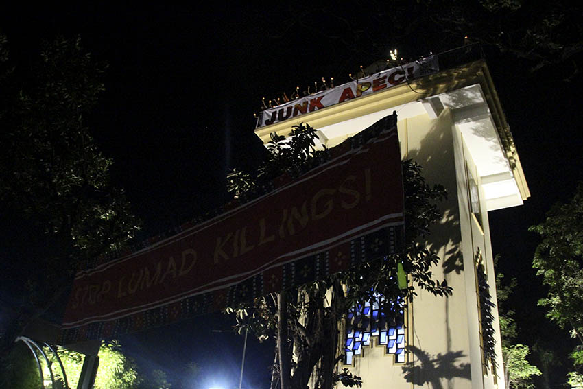 Church leaders and indigenous peoples hang tarpaulins on both sides of the bell towers of the National Shrine Mother of Perpetual Help Redemptorist church in Baclaran, Parañaque City. (Earl O. Condeza/davaotoday.com)